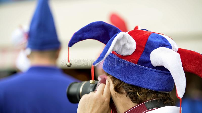 Ridiculously dressed and excited fan taking photos on camera, waiting for match stock image