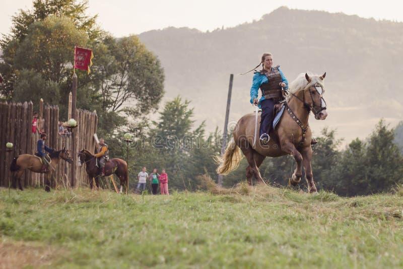 Ridind da menina um cavalo no festival de Tustan em Urych, Ucrânia, Augus foto de stock