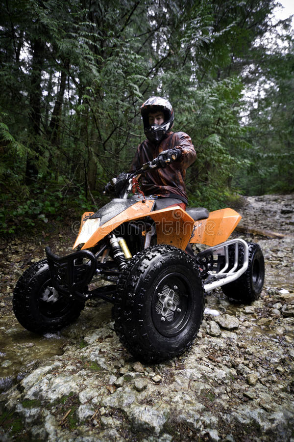 Riding ATV in mountains. Teen aged boy riding quad in the forest. . Subject is approaching and facing camera stock photos