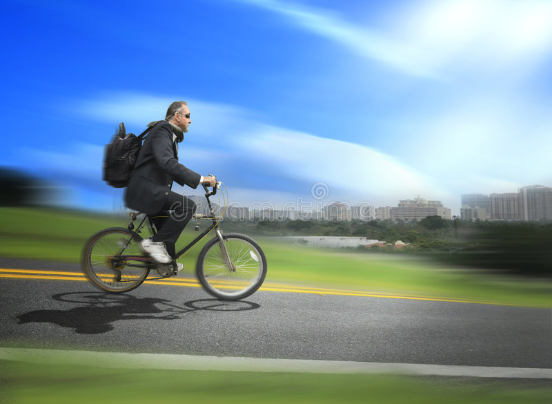 Riding bicycle. A business man wearing sneakers rides his bike to work instead of driving a car. Concept for global warming and the effort to stop it by reducing