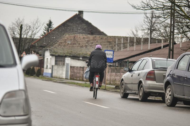 Riding bicycle along the street. Riding bicycle on a east european village stock image