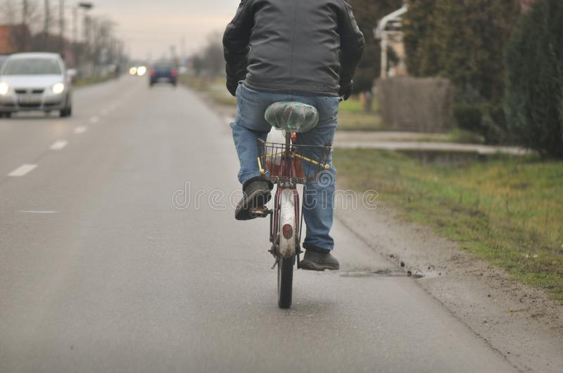 Riding bicycle along the street. Riding bicycle on a east european village stock photo