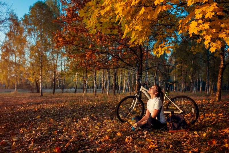 Riding bicycle in autumn forest. Young woman biker relaxing after exercising on bike. Healthy lifestyle royalty free stock photo