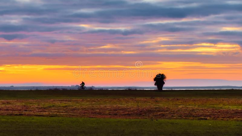 Riding the bicycle into the beautiful orange sunrise at Claddagh, Galway. Man in reflective shirt riding his bicycle by the Atlantic ocean early morning into the royalty free stock photos