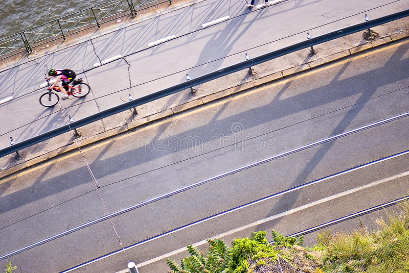 Riding bicycle... Good quality photo of an empty asphalt road somewhere over the bridge. Just lonely man rides on bicycle. Good sharpness, bright colors royalty free stock photos