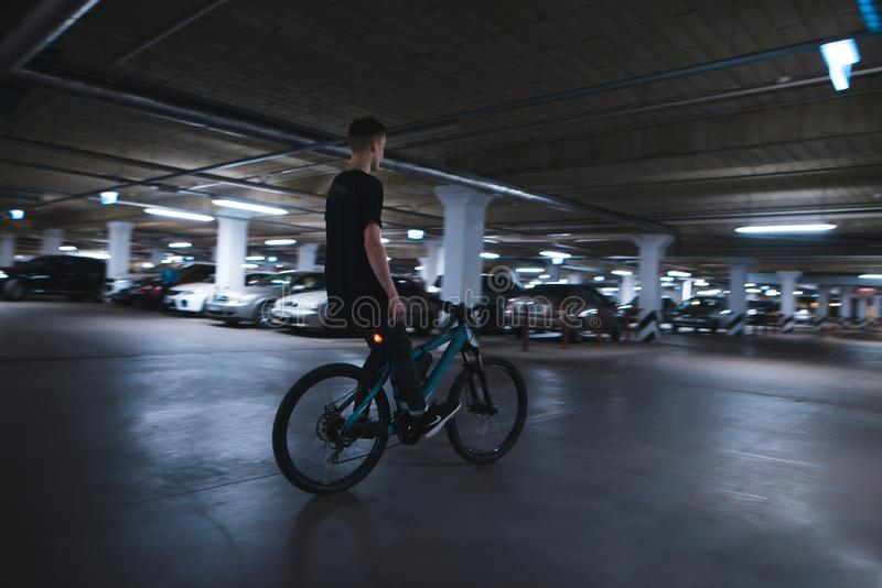 bike without hands on underground parking. An extreme man rides a bike on the parking lot stock images