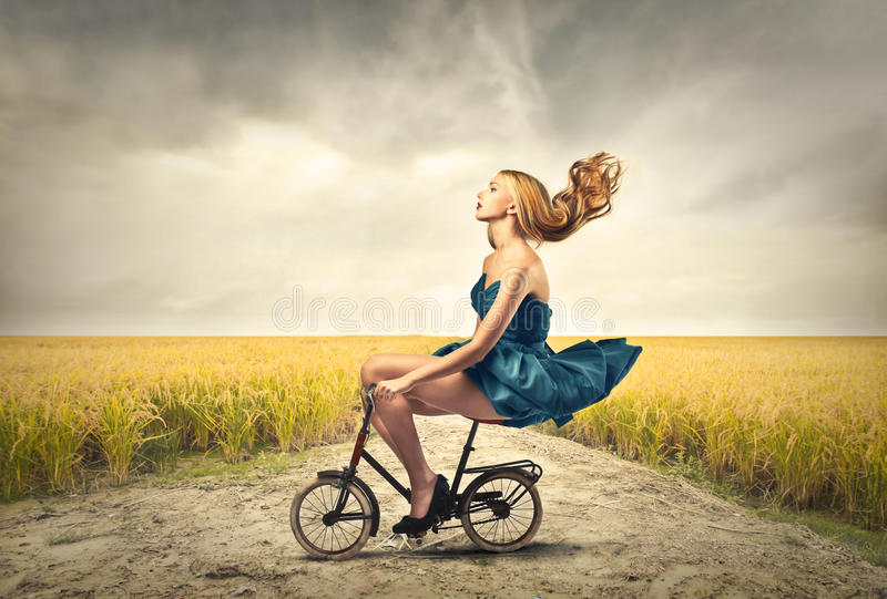 Riding a bike. Woman riding a small bike in the countryside royalty free stock image