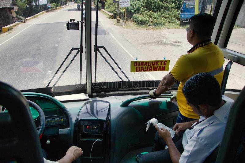 Riding the Ceres Liner Bus to Dumaguete from Bayawan. A Ceres Liner Bus Driver and crew look onward as they travel en route to the next destination. One man stock photo