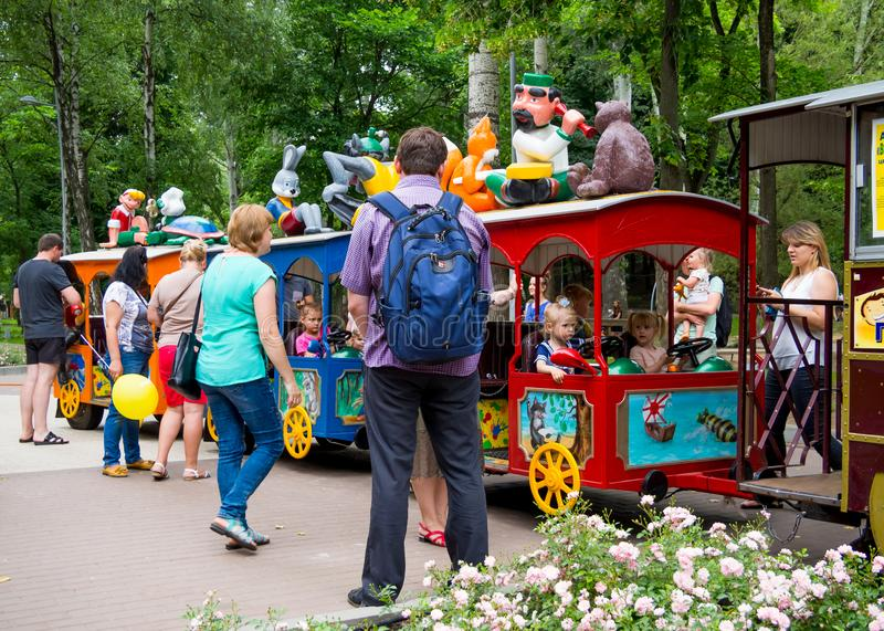 Riding of children with their parents on the attraction `Train` in the central park of the city stock photos