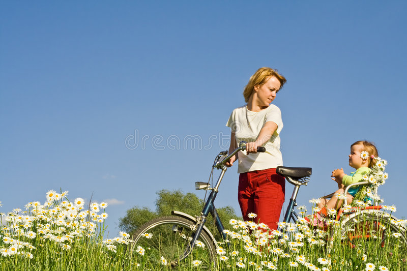 Riding through the daisy field. Woman and little girl riding a bike through a daisy field against blue sku stock image