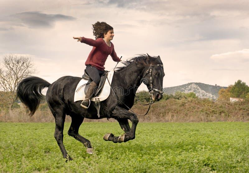 Riding girl and black stallion royalty free stock image