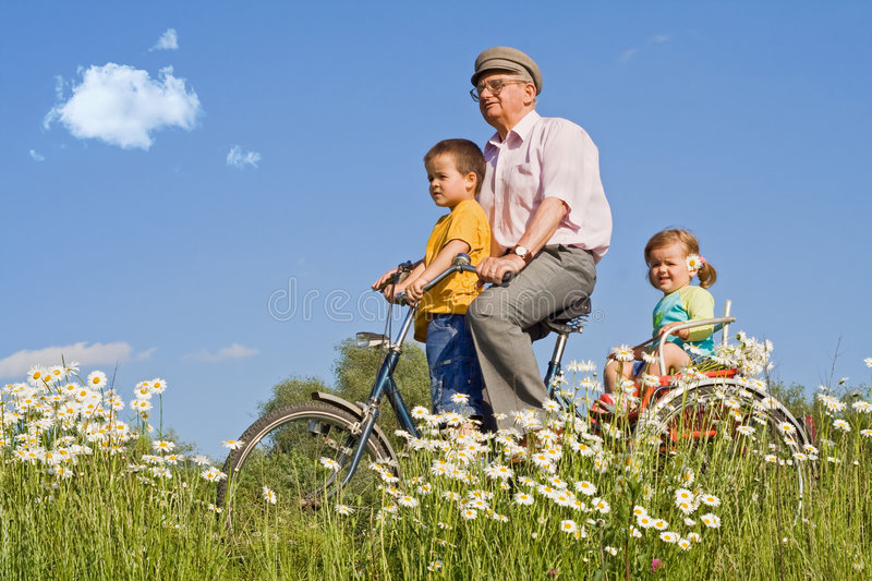 Riding with grandpa on a bike stock image