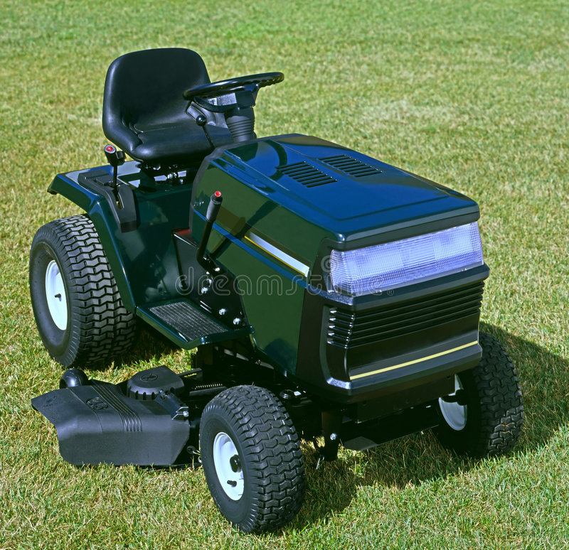 Riding lawnmower. Closeup of a riding lawnmower, sitting vacant on a green grass stock images