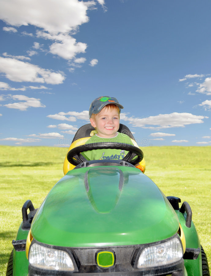 Riding Mower. A little boy sitting on his daddy's green lawn mower royalty free stock image