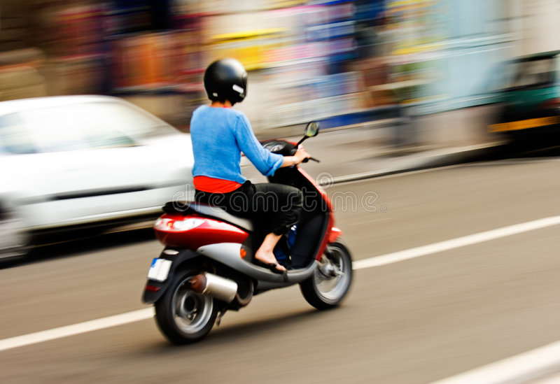 Riding a scooter stock images