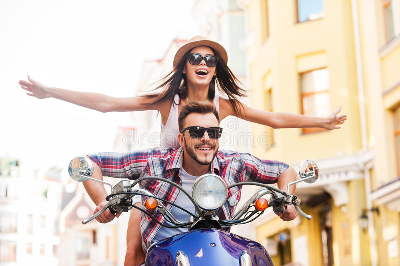 Riding scooter together. Beautiful young couple riding scooter together while happy women keeping arms outstretched and smiling stock image