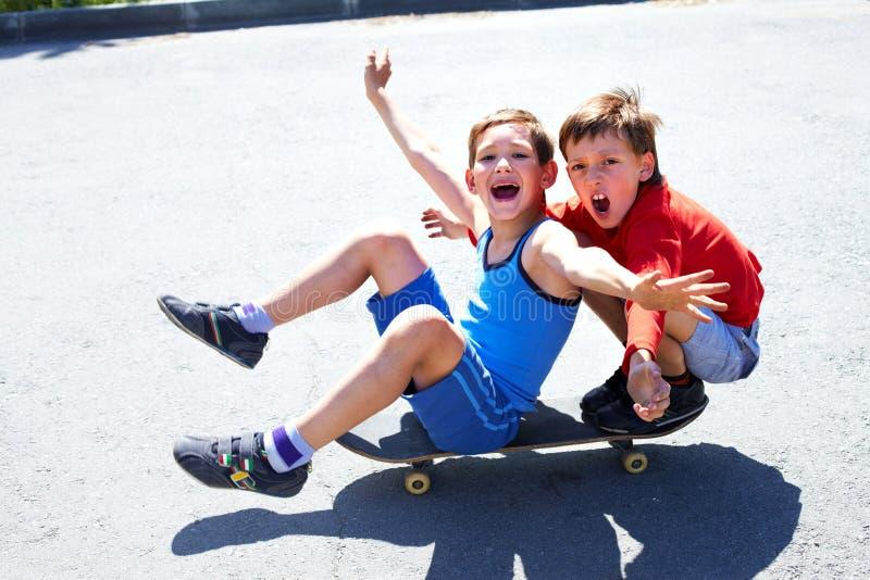 Riding skateboard. Two cheerful boys sitting on skateboard stock photography