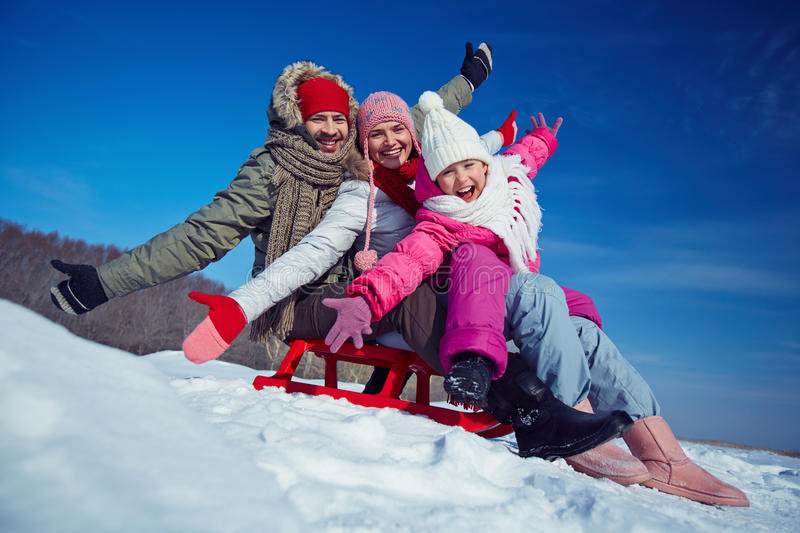 Riding on sledge. Father, mother and daughter on sledge having fun in winter royalty free stock photos