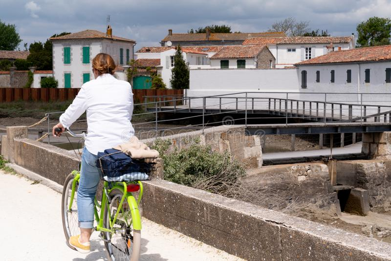 Riding tourist woman on bicycle at the coast on village on Ile de Ré island in France west stock photos