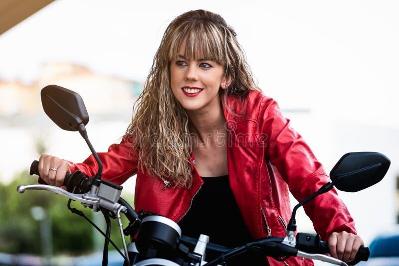 Ridint hermoso de la mujer joven en la motocicleta imagenes de archivo