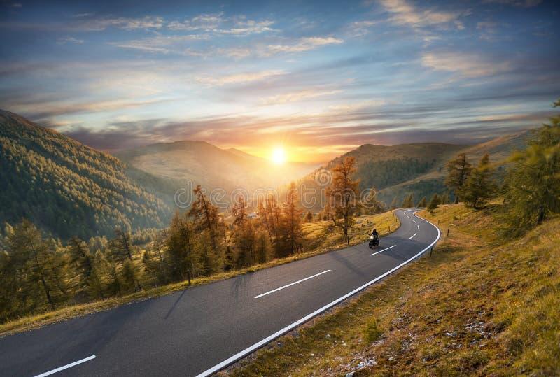 Ridning för motorcykelchaufför i alpin huvudväg Utomhus- fotografi, royaltyfria bilder