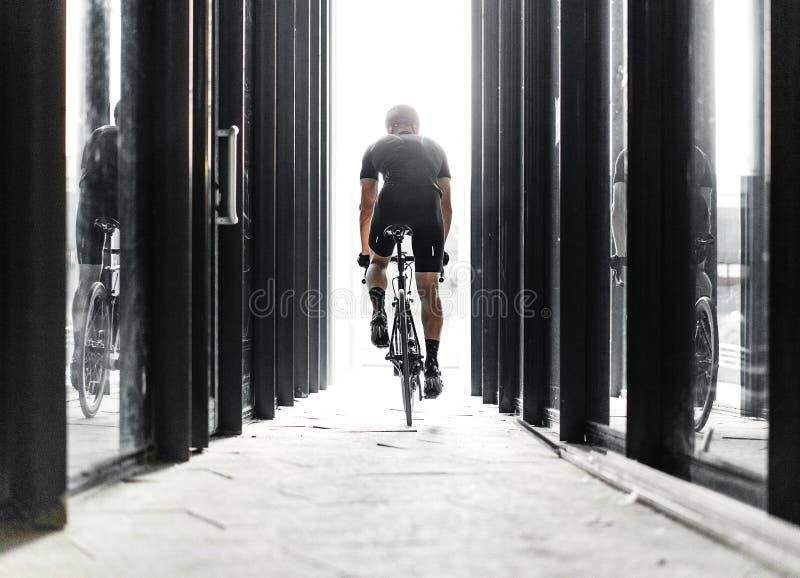 Ridning för sportcykelman inom den stads- glass tunnelen med ljus royaltyfri foto