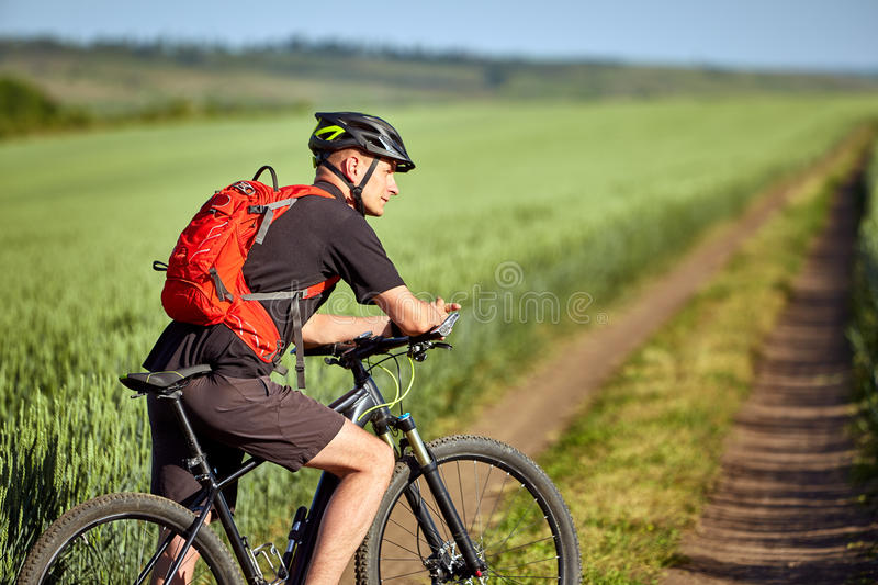 Ridning för ung man på en cykel på grön äng med en ryggsäck arkivfoto