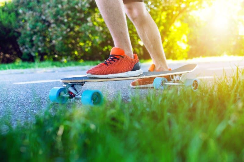 Ridning för ung man på en longboard Longboard på vägen i soligt väder Folk runt om skateboarden arkivfoto
