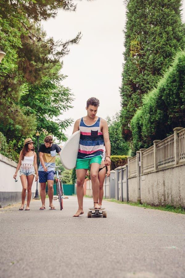 Ridning för ung man på skridsko- och innehavsurfingbrädan arkivbild