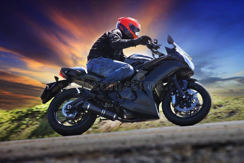 Ridningmotorcykel för ung man på kurva av agaen för asfaltlandsväg royaltyfri fotografi