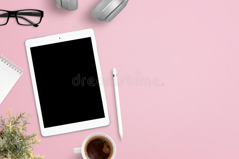 Riduca in pani il modello sullo scrittorio rosa del lavoro circondato con le cuffie, i vetri, il blocco note, la pianta, la tazza fotografia stock libera da diritti