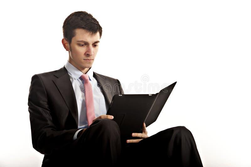 Ridurre in pani del calcolatore di seduta e della lettura dell'uomo d'affari fotografie stock libere da diritti