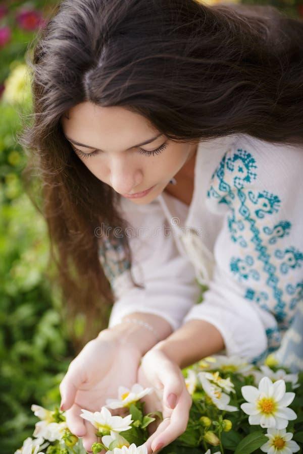 Riechende Blumen der Frau lizenzfreie stockbilder