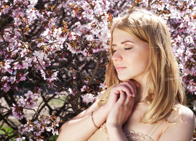 Riechende Blumen der Frau in blühendem Kirschblüte-Garten stockfoto