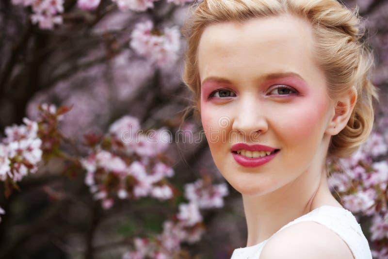 Riechende Blumen der Frau in blühendem Kirschblüte-Garten lizenzfreie stockfotos