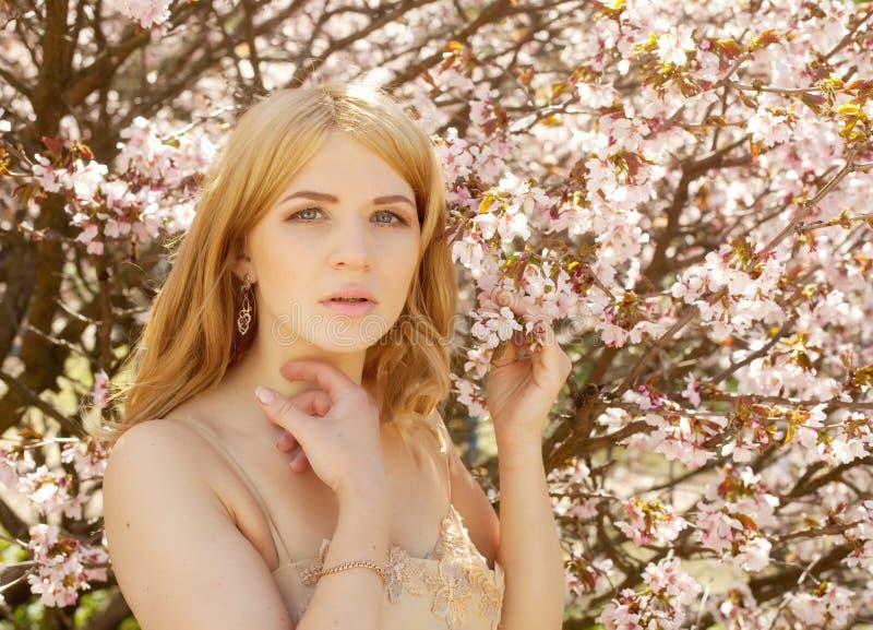Riechende Blumen der jungen blonden Frau lizenzfreie stockfotografie