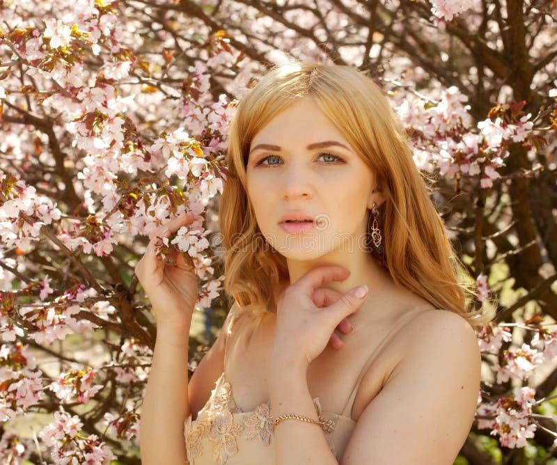 Riechende Blumen der jungen blonden Frau lizenzfreie stockfotos