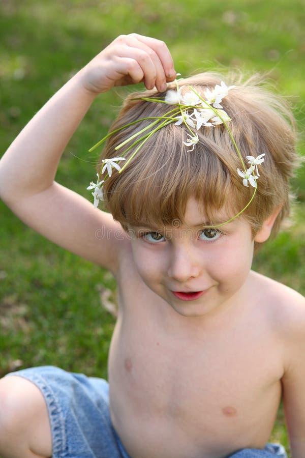 Riechende Blumen des Jungen stockfotografie