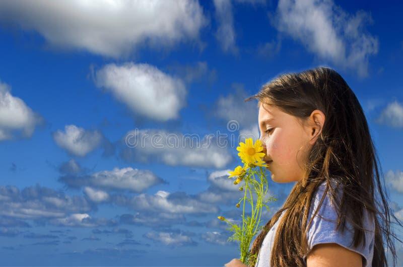 Riechende Blumen des jungen Mädchens lizenzfreie stockbilder