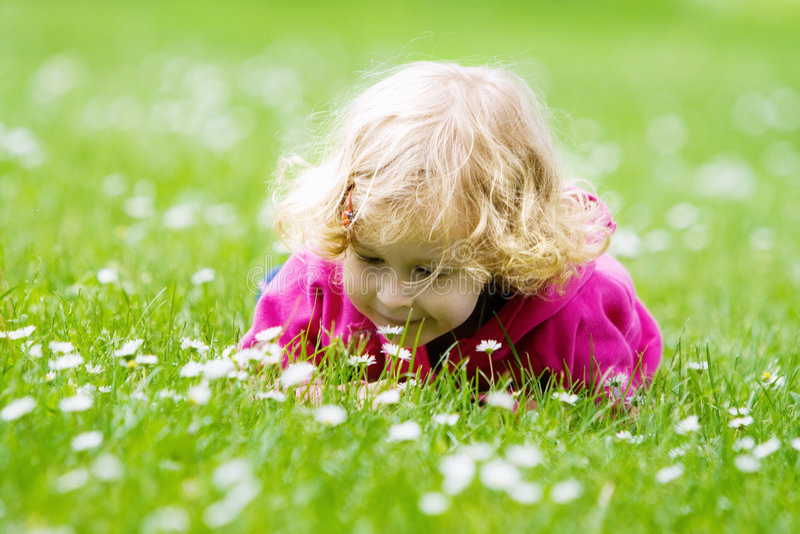 Riechende Blumen des kleinen Mädchens stockbilder