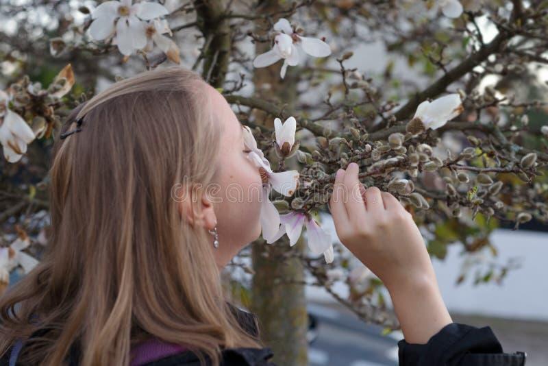 Riechende Blumenblüte der glücklichen jungen Mode lizenzfreies stockfoto