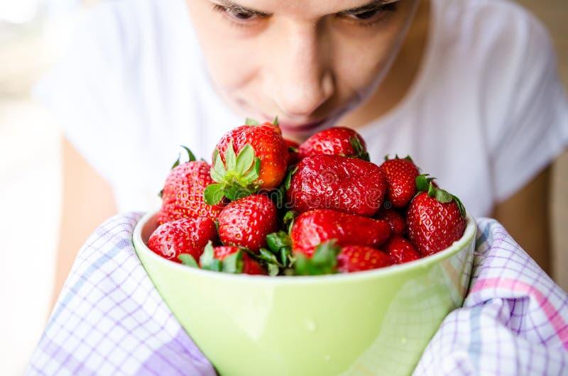 Riechende Erdbeeren der Frau lizenzfreie stockfotografie