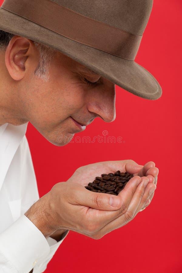 Riechende Kaffeebohnen des Mannes stockfotos