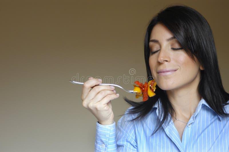 Riechende Nahrung der Frau lizenzfreie stockbilder