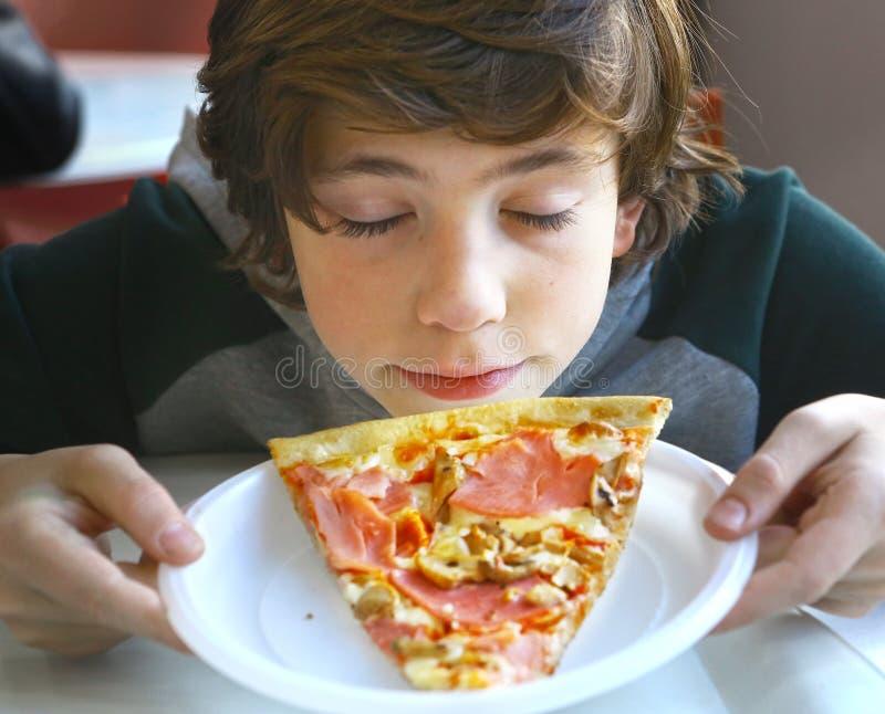 Riechende Pizza des netten kleinen jugendlichen Jungen lizenzfreie stockfotos