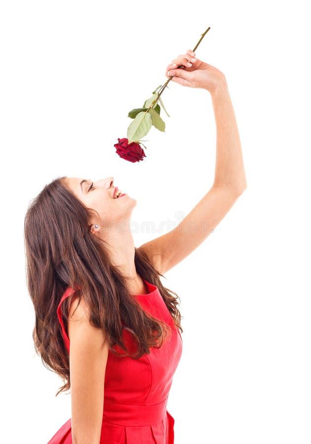 Riechende Rotrose der Frau lizenzfreie stockfotos