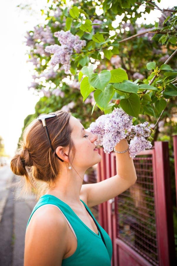 Riechende weiße Jasminblumen der jungen Frau lizenzfreie stockfotografie