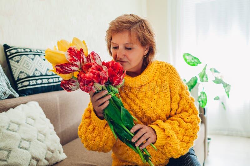 Riechender Blumenstrauß der älteren Frau von Tulpen von ihren Kindern zu Hause Mutter ` s Tagesgeschenk stockfoto