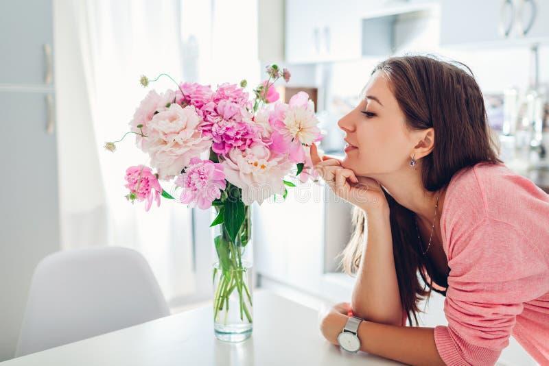 Riechender Blumenstrau? der Frau von Pfingstrosen Hausfrau, die Dekor und Innenraum der K?che genie?t S??es Haus lizenzfreies stockbild