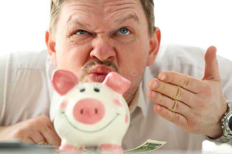 Riechender Geruch des lustigen Geschäftsmannes des Geldes vom piggybank lizenzfreies stockbild